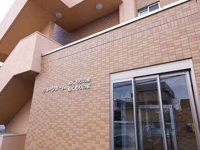 ベージュと茶色のタイルを組み合わせたエントランスに、ベージュの文字で施設名が記されている。ドアは透明なガラスである。