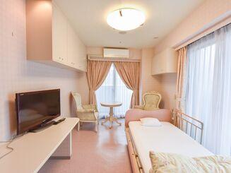 ... ピンク色を基調としたかわいらしい居室。複数の吊戸棚の収納が